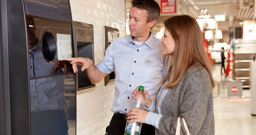 Image of retailer with shopper at reverse vending machine in return-to-retail model